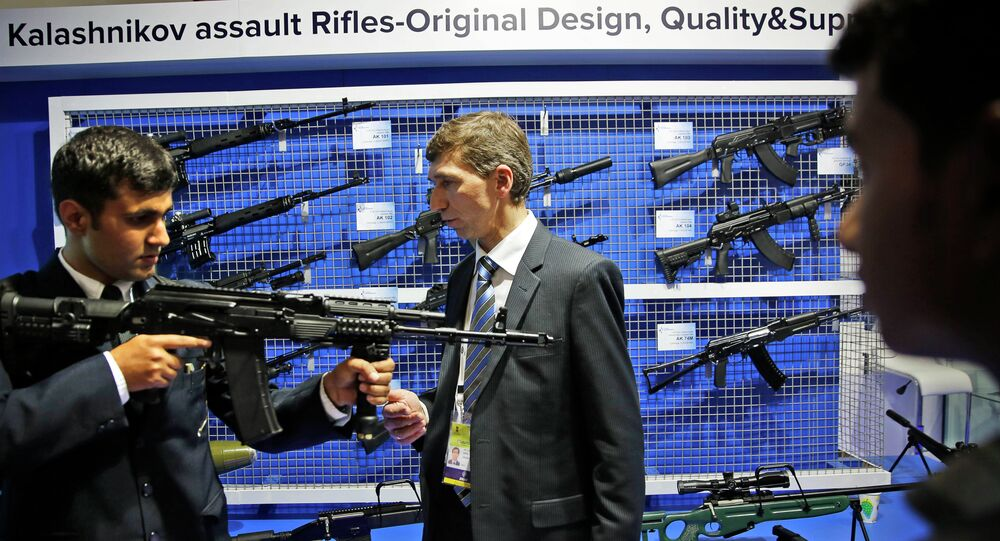 A Russian exhibitor from Kalashnikov, center, explains the working of an AK-104 at the 8th International Land and Naval Defense system exhibition, in New Delhi, India, Thursday, Feb. 6, 2014