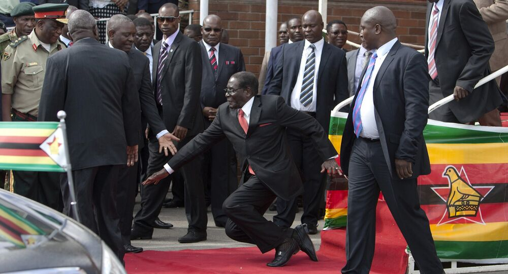 Zimbabwean President Robert Mugabe, center, falls after addressing supporters upon his return from an African Union meeting in Ethiopia, Wednesday, Feb. 4, 2015