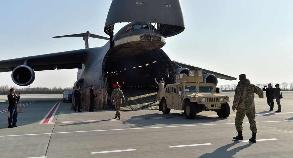 Ukrainian and US servicemen unload armoured cars from a plane at Kiev airport on March 25, 2015 during a welcoming ceremony of the first US plane delivery of non-lethal aid, including 10 Humvee vehicles