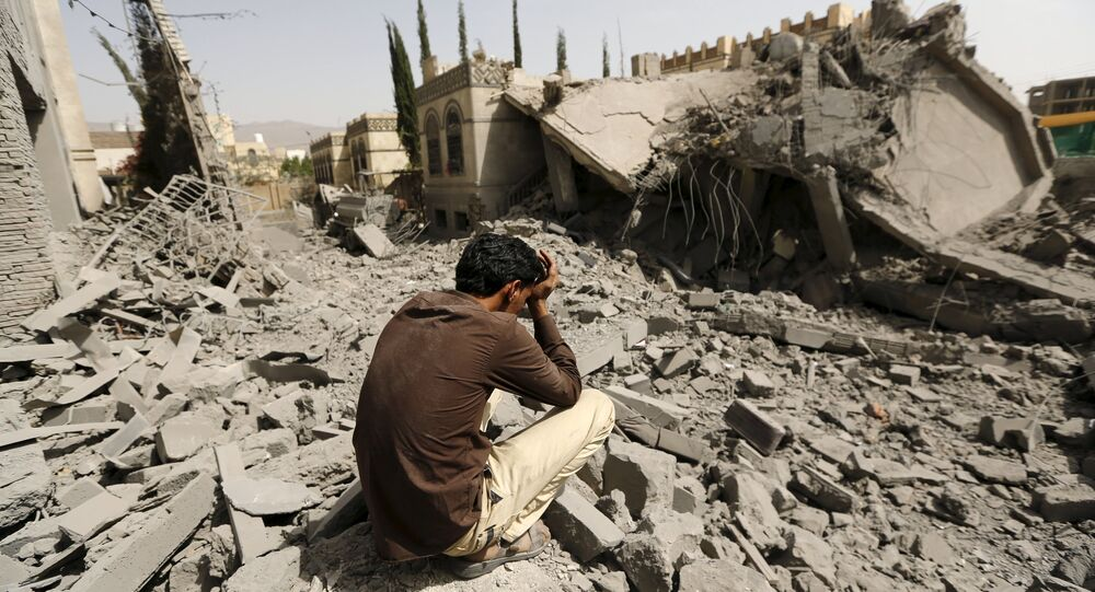 A guard sits on the rubble of the house of Brigadier Fouad al-Emad, an army commander loyal to the Houthis, after air strikes destroyed it in Sanaa, Yemen June 15, 2015