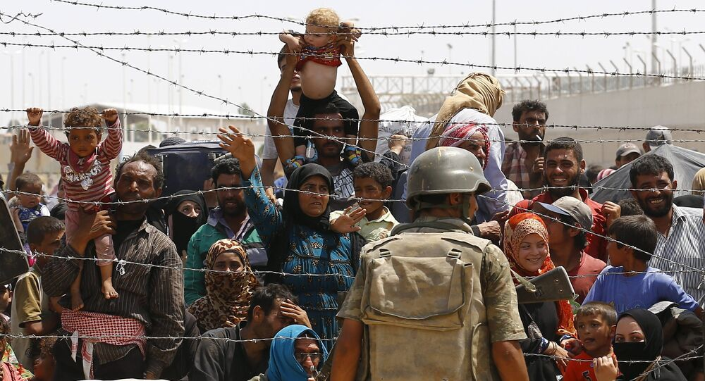 Syrian refugees wait behind the border fences to cross into Turkey at Akcakale border gate in Sanliurfa province, Turkey, June 15, 2015