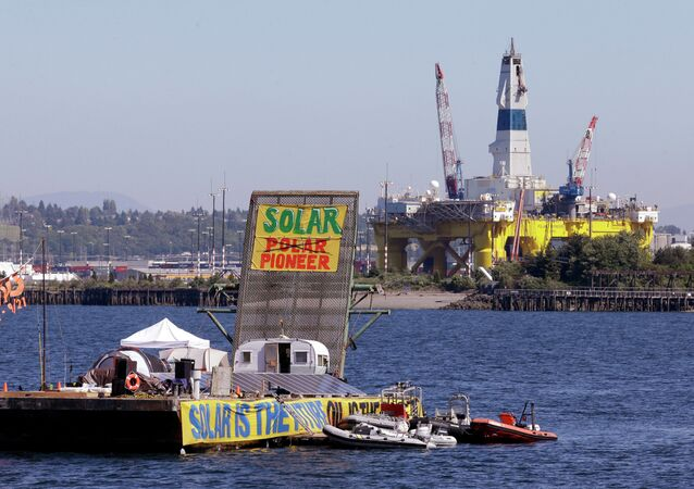 In this photo taken Monday, June 8, 2015, a barge used by protesters is anchored in view of the Arctic oil drilling rig Polar Pioneer behind, in Elliott Bay in Seattle