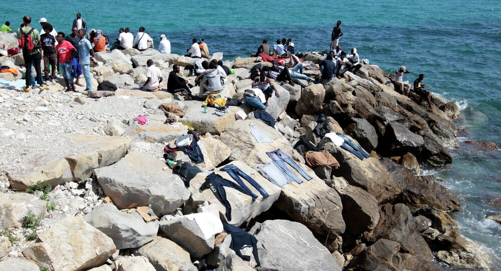 Migrants dry their clothes on rocks as they wait to cross into France, in the Italian city of Ventimiglia, on the French-Italian border, on June 14, 2015