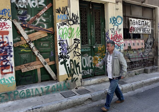 A man walks past abandoned buildings with 'for sale' sign in central Athens, on May 13, 2015.