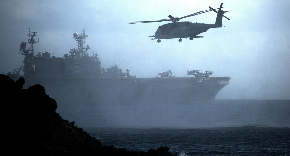 A CH-53E Super Stallion helicopter flies ahead of the amphibious assault ship USS Peleliu off the coast of Hawaii during Rim of the Pacific exercise in 2014.