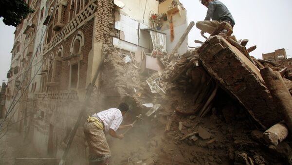 A man searches for survivors under the rubble of houses destroyed by Saudi airstrikes in the old city of Sanaa, Yemen, Friday, June 12, 2015 - Sputnik International
