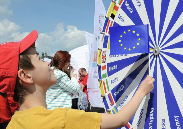 A boy holding a EU flag looks at a wheel with the names of all European Union countries during a picnic marking ten years since Poland joined the EU, in Warsaw, Poland, Thursday, May 1, 2014