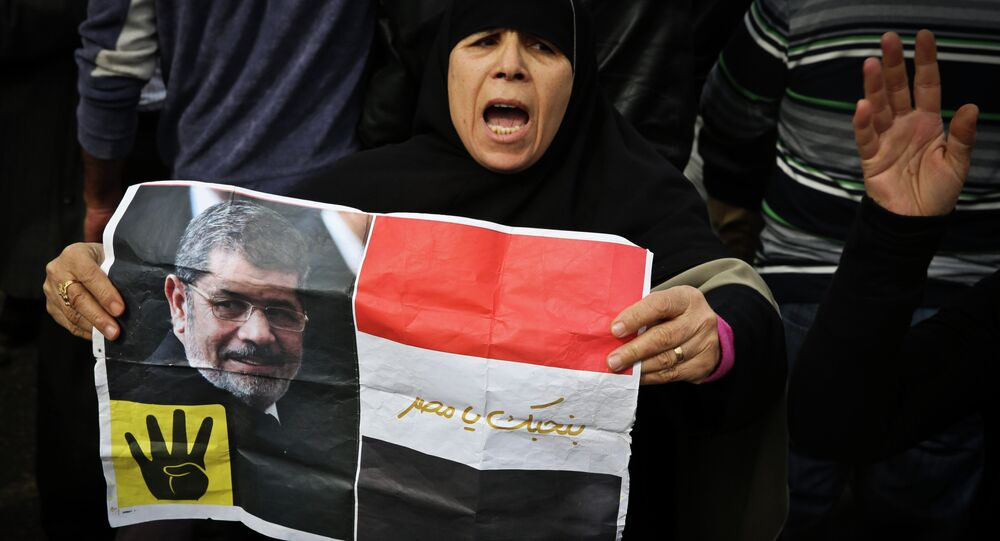 A supporter of the Muslim Brotherhood movement holds a placard showing ousted president Mohamed Morsi during a demonstration on January 24, 2015 in the Cairo district of Heliopolis