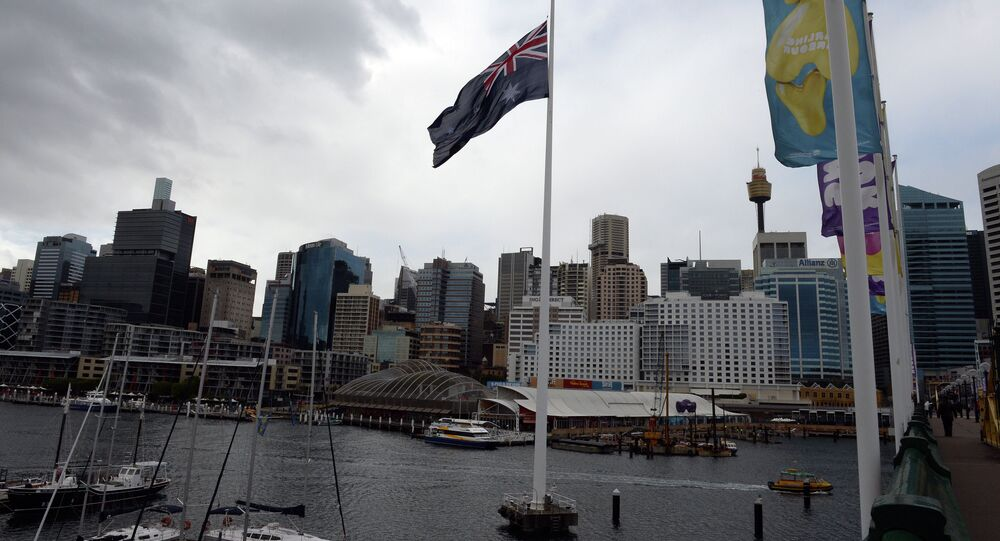 An Australian national flag flies in front of the city skyline at the Darling Harbour in Sydney on July 19, 2014