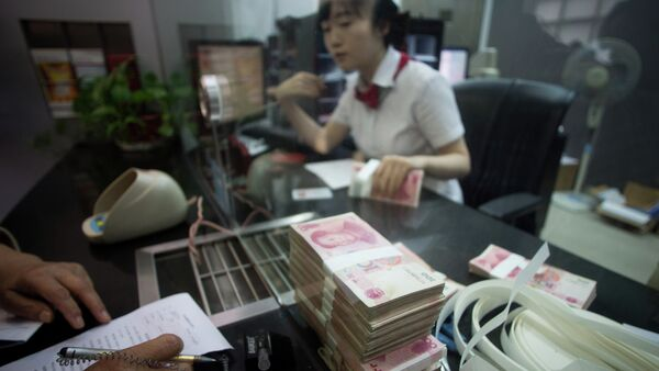 This picture taken on September 24, 2014 shows a worker of an Industrial and Commercial Bank of China Ltd (ICBC) branch counts money as she serves a customer in the China (Shanghai) Pilot Free Trade zone during a media trip - Sputnik International