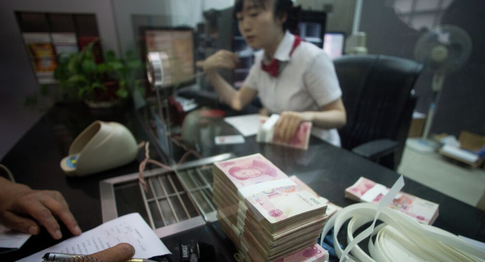 This picture taken on September 24, 2014 shows a worker of an Industrial and Commercial Bank of China Ltd (ICBC) branch counts money as she serves a customer in the China (Shanghai) Pilot Free Trade zone during a media trip