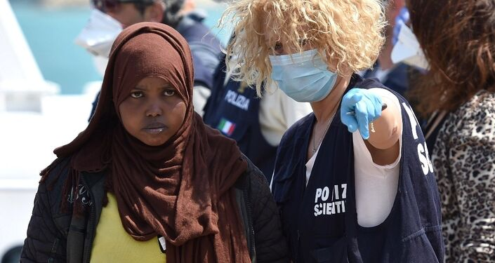 A forensic police officer gives indications to a woman as migrants arrived at Pozzallo's harbor near Ragusa, Sicily, Italy.