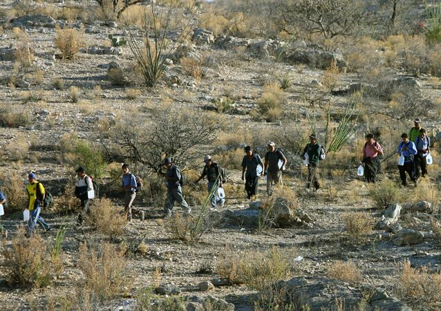 Mexican immigrants walk in line through the Arizona desert