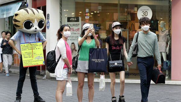 People wear masks as a precaution against the MERS virus as they walk in Myeongdong, one of Seoul's main shopping districts. - Sputnik International