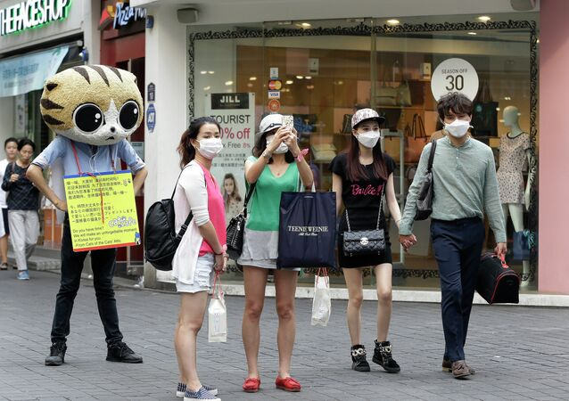 People wear masks as a precaution against the MERS virus as they walk in Myeongdong, one of Seoul's main shopping districts.