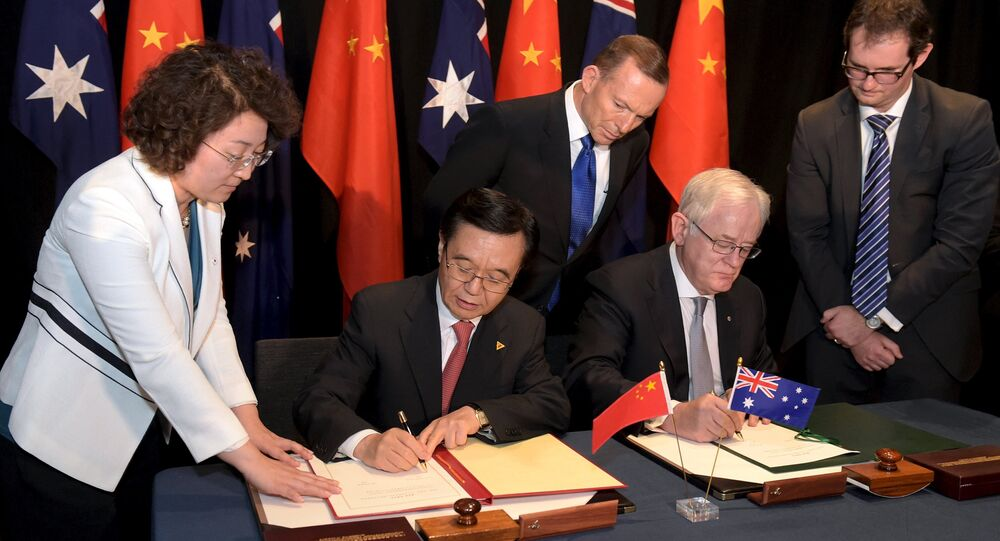 Australian Prime Minister Tony Abbott (C) watches as China's Minister of Commerce Gao Hucheng (2nd L) and Australian Minister for Trade Andrew Robb (2nd R) sign a trade agreement during an official signing ceremony in Canberra June 17, 2015