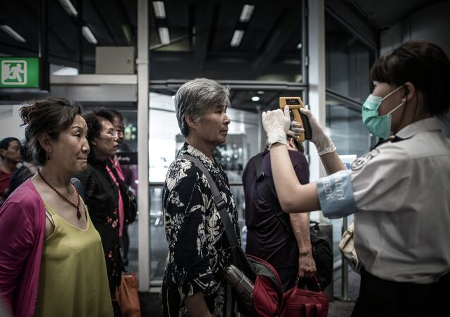 Passengers get their temperature checked as part of preventive measures against the spread of Middle East Respiratory Syndrome (MERS) at the Hong Kong international airport on June 5, 2015
