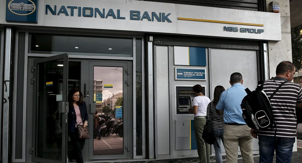 People line up at an ATM machine outside a National Bank branch in Athens