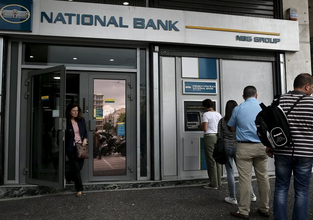 People line up at an ATM machine outside a National Bank branch in Athens.
