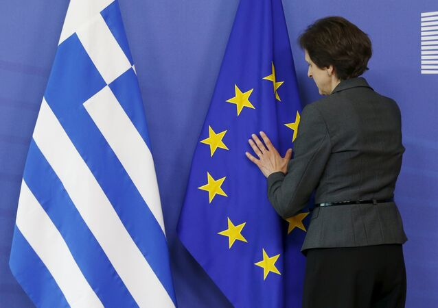 A worker adjusts flags ahead of the meeting between Greek Prime Minister Alexis Tsipras and European Commission President Jean-Claude Juncker at the EU Commission headquarters in Brussels, Belgium, June 3, 2015.