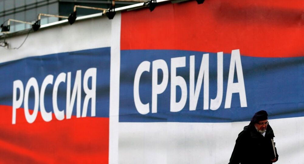 A man passes by a billboards reading 'Russia' , left and 'Serbia' in Belgrade, Serbia.