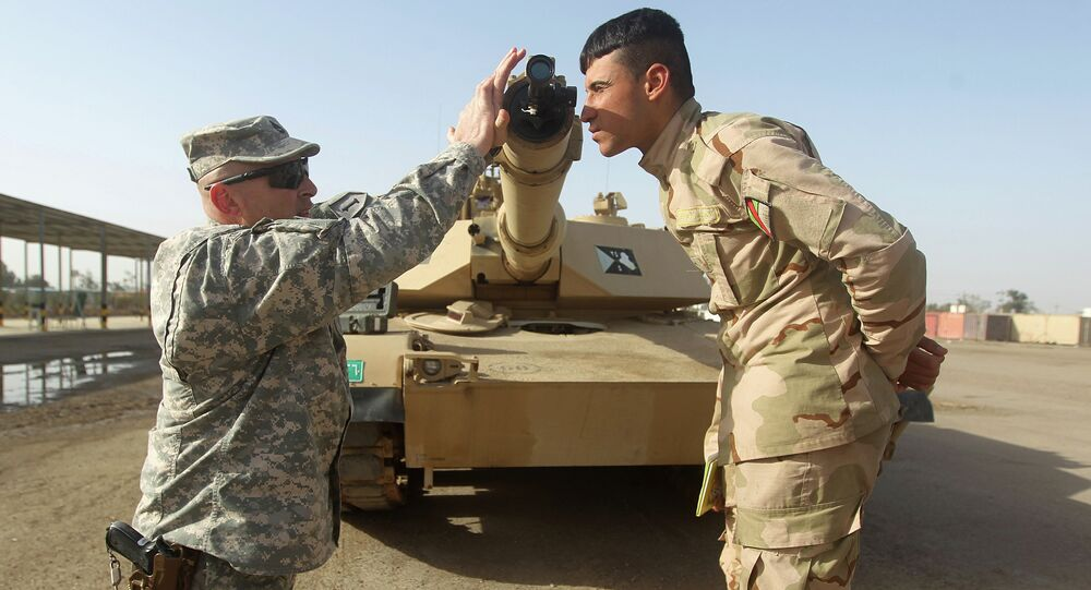 American military trainer shows an Iraqi soldier how to use a collimator to calibrate the gun barrel of an Abrams tank during a training session at the Taji base complex, which hosts Iraqi and US troops