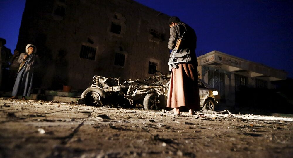 An armed man looks at the wreckage of a car at the site of a car bomb attack in Yemen's catpital Sanaa June 17, 2015