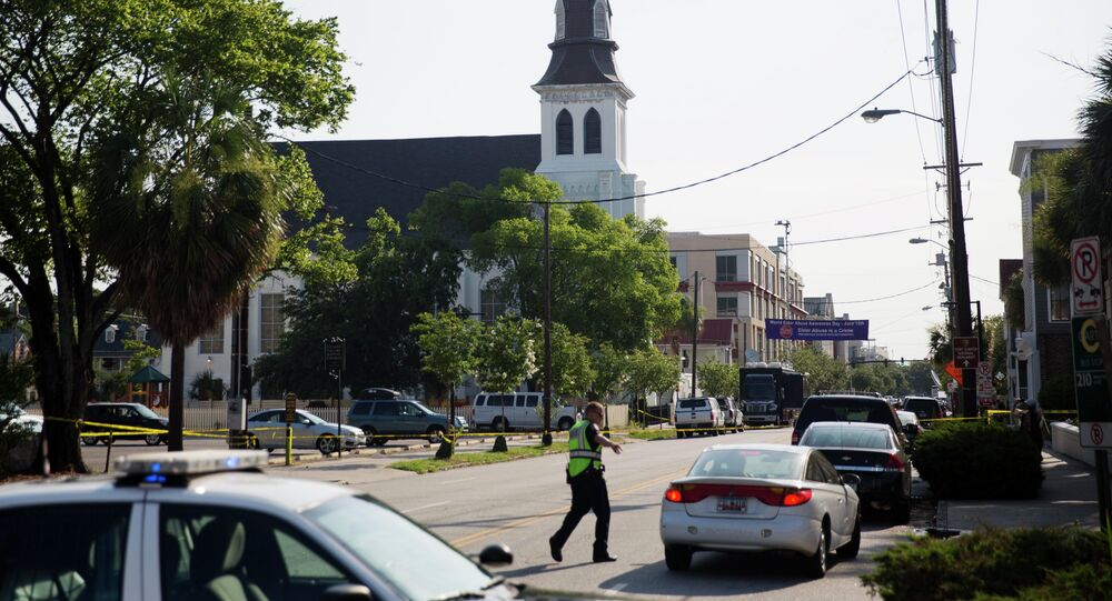 The steeple of Emanuel AME Church rises above the street as a police officer tells a car to move as the area is closed off following Wednesday's shooting, Thursday, June 18, 2015 in Charleston, S.C.