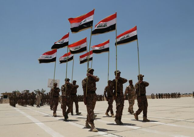 Sunni tribal volunteers with national flags march during their graduation ceremony.