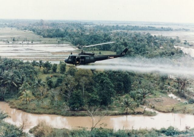 US Army helicopter sprays Agent Orange over Vietnamese fields.