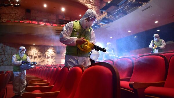 South Korean workers wearing protective gear fumigate a theater at the Sejong Culture Center in Seoul - Sputnik International