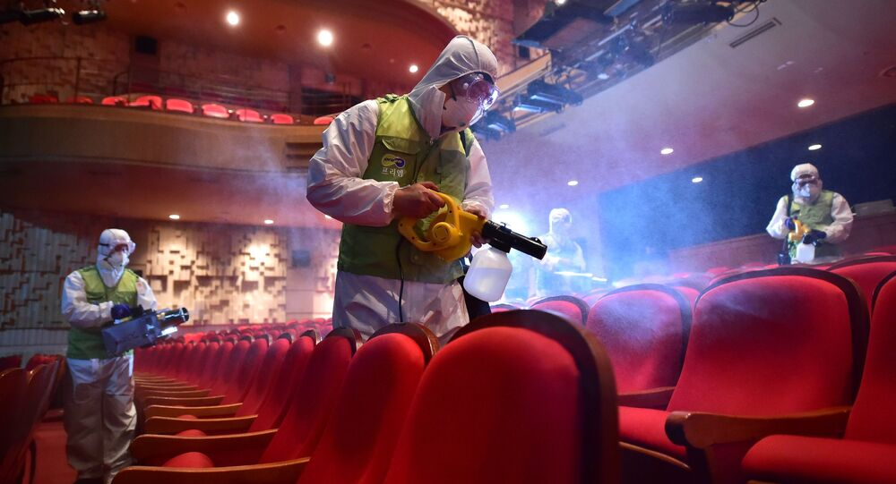 South Korean workers wearing protective gear fumigate a theater at the Sejong Culture Center in Seoul