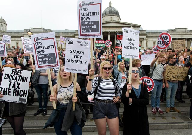 Protestors hold placards as they listen to speeches during an anti-austerity demonstration in London