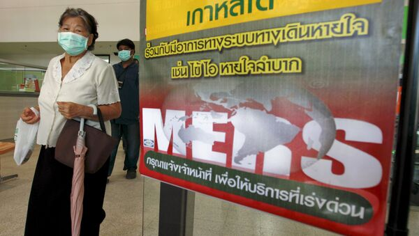 A woman wearing a mask walks past an information banner on Middle East Respiratory Syndrome (MERS) at the entrance of Bamrasnaradura Infectious Diseases Institute at a hospital in Nonthaburi province, on the outskirts of Bangkok, Thailand, June 19, 2015 - Sputnik International