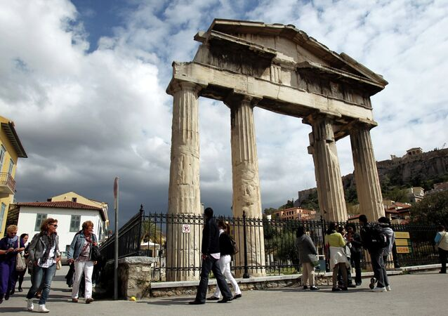 Tourists  walk outside the gate of the ancient Roman agora in Athens, Greece