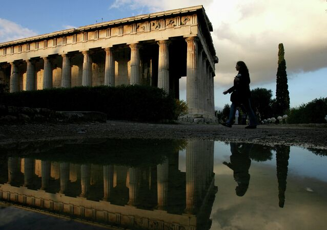 A tourist is reflected in a rain puddle as she walks past the 2,400-year-old temple of Ifestos in the ancient Agora of Athens, Greece