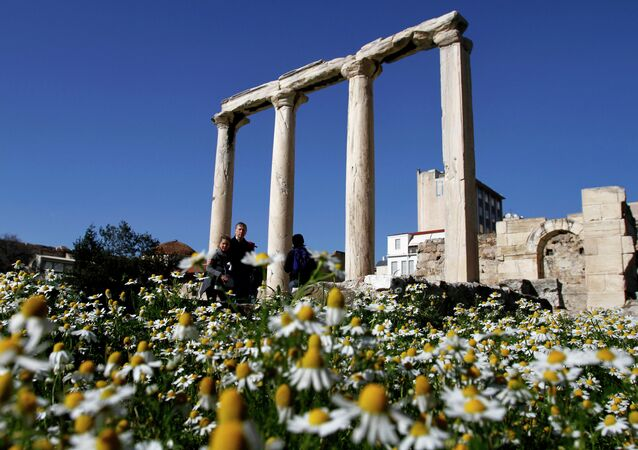 Tourist walk among daisies and a part of the ancient building of Hadrian's Library near Monastiraki square, in Athens, Greece.