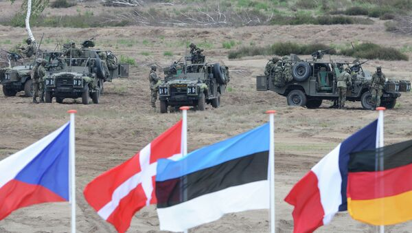 Flags wave in front of soldiers who take positions with their army vehicles during the NATO Noble Jump exercise on a training range near Swietoszow Zagan, Poland, Thursday, June 18, 2015 - Sputnik International