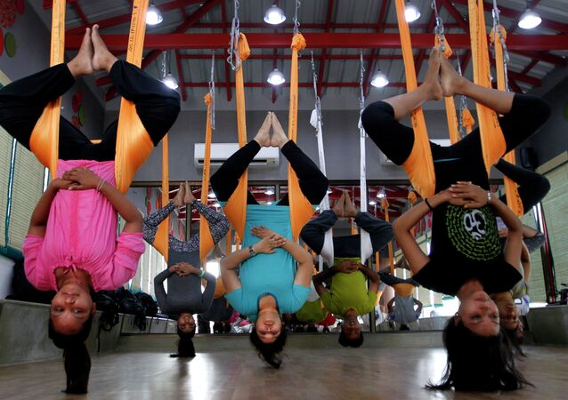 In this Thursday, June 18, 2015, photo, Indians perform anti gravity aerial yoga in Ahmadabad, India