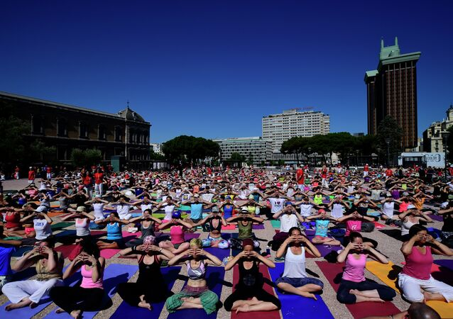 Participants take part in a mass yoga session to mark International Yoga Day at Colon square in Madrid on June 21, 2015
