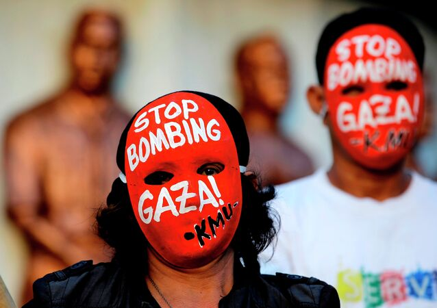Masked protesters hold a rally against the bombings in Gaza