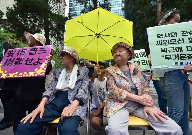 South Korean former comfort women Kim Bok-Dong (L) and Gil Won-Ok (R), who were forced to serve as sex slaves for Japanese troops during World War II, sit under a yellow umbrella during a press conference outside the Japanese embassy in Seoul on June 23, 2015.