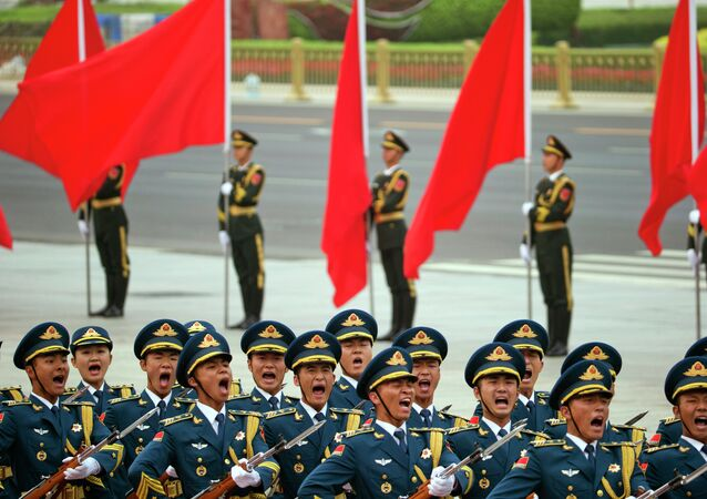 Members of a Chinese honor guard march in formation.
