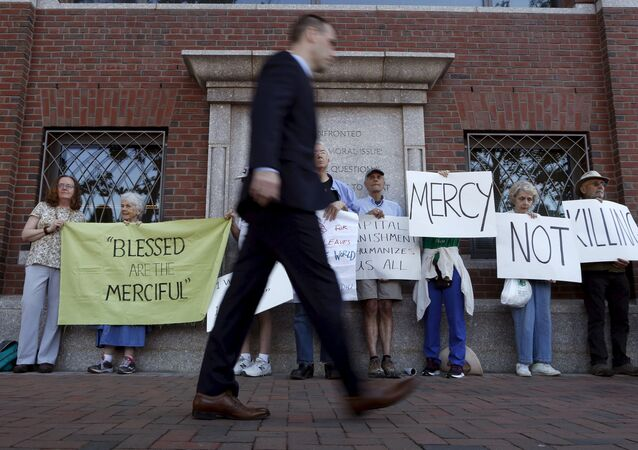 A pedestrian walks past death penalty protesters before the formal sentencing of convicted Boston Marathon bomber Dzhokhar Tsarnaev at the federal courthouse in Boston, Massachusetts June 24, 2015