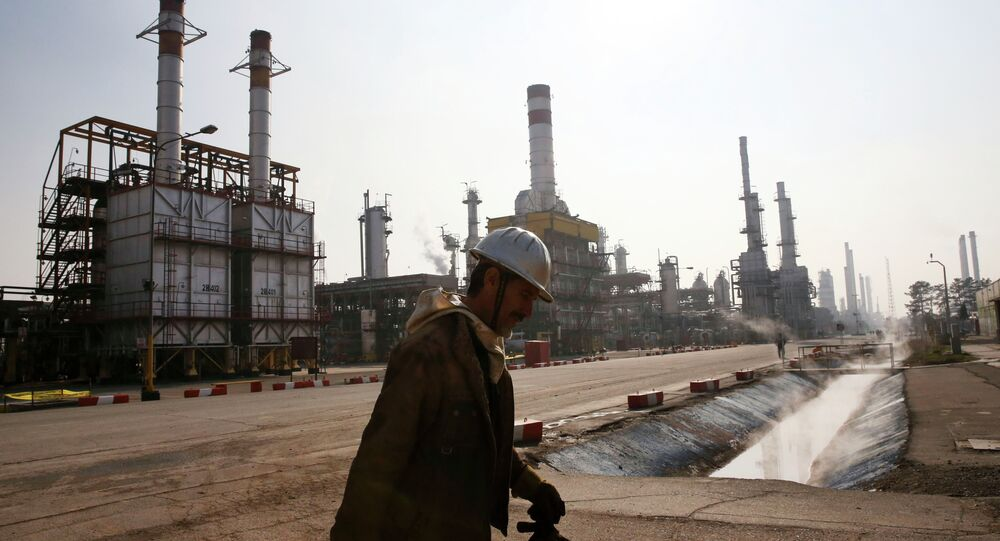 An Iranian oil worker makes his way through Tehran's oil refinery south of the capital Tehran, Iran, Monday, Dec. 22, 2014