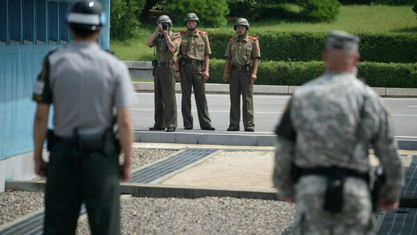 North Korean soldiers (C) take photos towards a South Korean soldier (L) and a US soldier (R) standing before the military demarcation line (lower C) seperating North and South Korea within the Joint Security Area (JSA) at Panmunjom on July 27, 2014 - Sputnik International