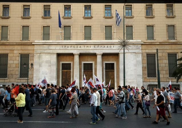 Members of the Communist-affiliated PAME labor union pass in front of the Bank of Greece during an anti-austerity protest in Athens on Tuesday, June 23, 2015