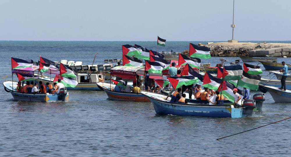 Palestinians hold their national flag as they ride boats during a rally to show support for activists aboard a flotilla of boats who are soon to set sail for Gaza in a fresh bid to break Israel's blockade of the territory, at the seaport of Gaza City on June 24, 2015