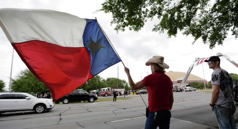 A man holds a Texas flag.