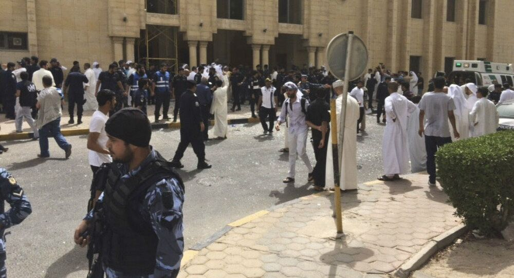 Security forces, officials and civilians gather outside of the Imam Sadiq Mosque after a deadly blast struck after Friday prayers in Kuwait City, Kuwait, Friday, June 26, 2015